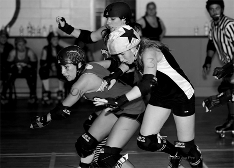Roller derby skater Prada G speeds up to block the opposing jammer
